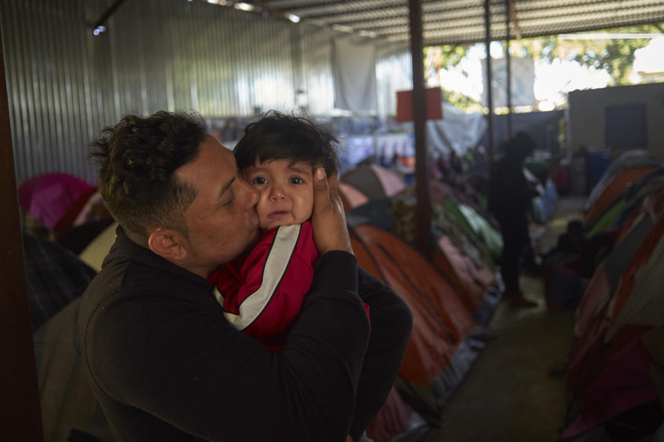 In this March 5, 2019, image, Juan Carlos Perla kisses his 10-month-old son, Joshua, inside a shelter for migrants in Tijuana, Mexico. After fleeing violence in El Salvador and requesting asylum in the United States, the family was returned to Tijuana to await their hearing in San Diego. They are one of the first families to contend with a new policy that makes asylum seekers stay in Mexico while their cases wind through U.S. immigration courts. (AP Photo/Gregory Bull)