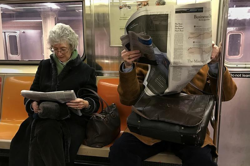 A couple of people ride the subway as they read newspapers as the train pulls into the Times Square stop in Manhattan