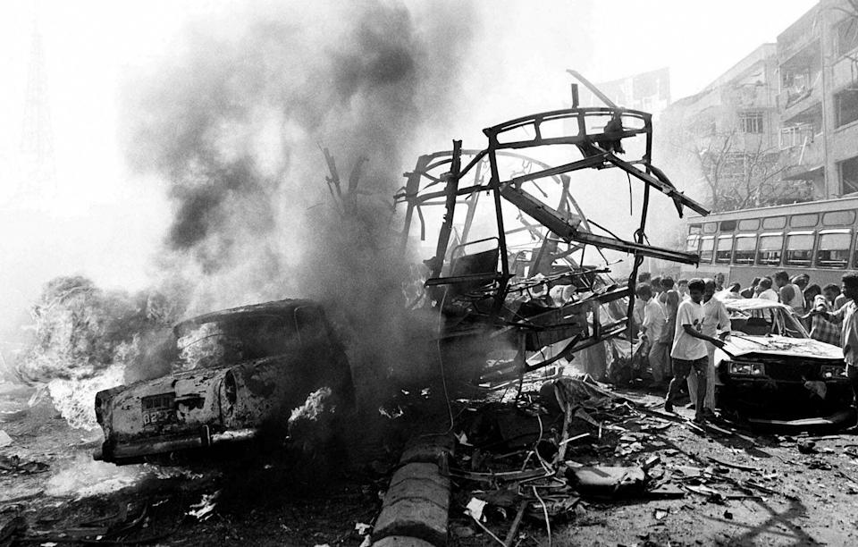 The skeletal remains of a transport bus are seen alongside burning vehicles and damaged buildings outside Bombay's Passport Office after a massive explosion, March 12, 1993. (AP Photo/Sherwin Crasto)