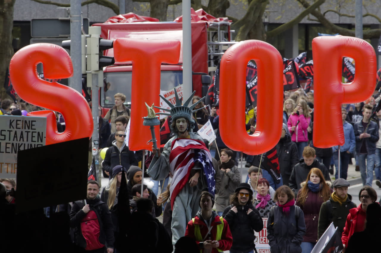 """A man on stilts dressed like the Statue of Liberty walks in front of balloons forming the slogan """"Stop TTIP"""" during a protest of thousands of demonstrators against the planned Transatlantic Trade and Investment Partnership (TTIP) and the Comprehensive Economic and Trade Agreement (CETA) ahead of a visit by President Obama in Hanover, Germany, April 23, 2016. (Markus Schreiber/AP)"""