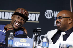 Floyd Mayweather Jr. (L) and Mayweather Promotions CEO Leonard Ellerbe, laugh during a press conference. (AP)