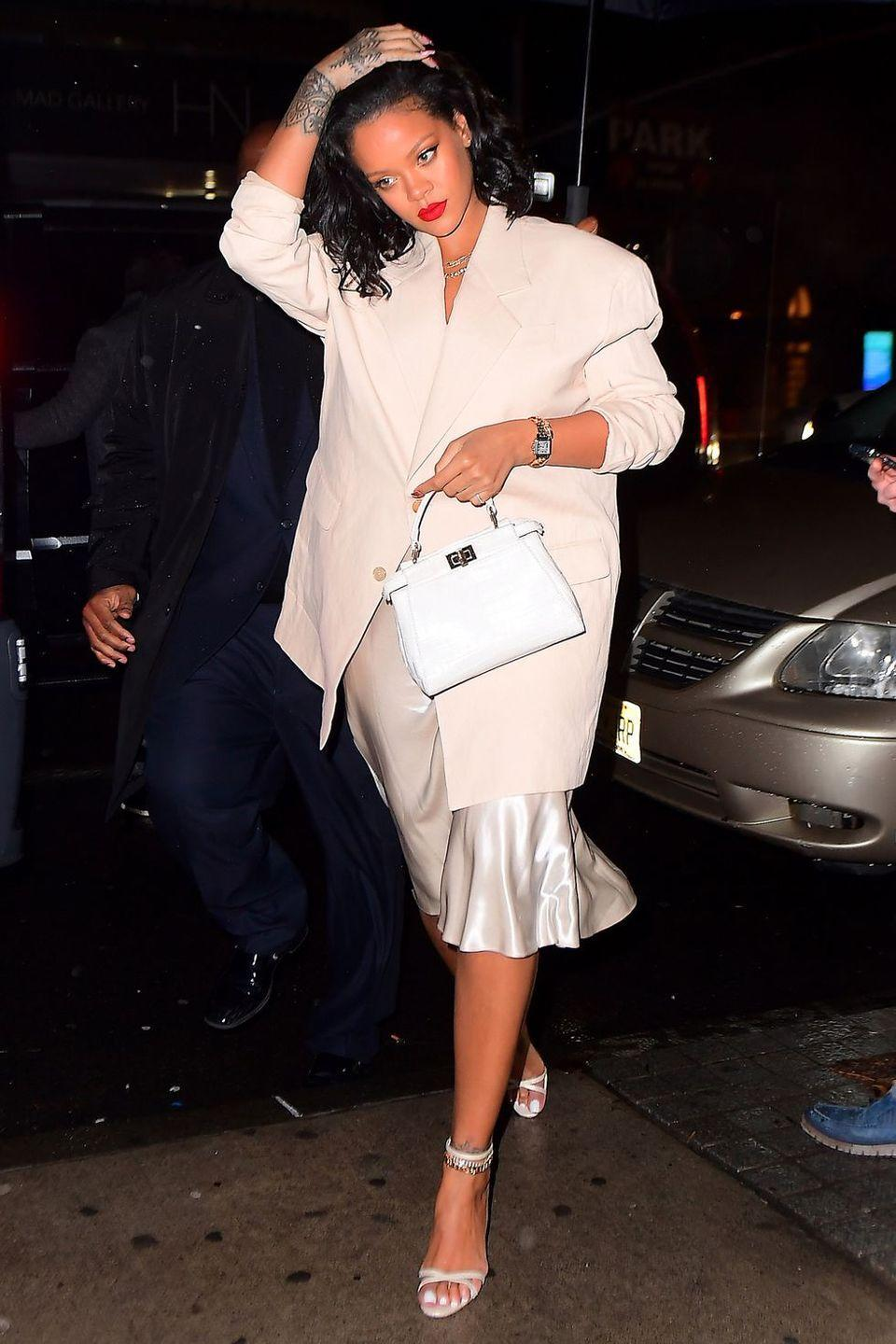 "<p>In a blush oversized blazer, champagne slip dress, heeled sandals, and a white Fendi mini peekaboo bag while out in NYC.</p><p><a class=""link rapid-noclick-resp"" href=""https://go.redirectingat.com?id=74968X1596630&url=https%3A%2F%2Fwww.net-a-porter.com%2Fus%2Fen%2Fproduct%2F895774%2Ffendi%2Fpeekaboo-mini-leather-shoulder-bag&sref=https%3A%2F%2Fwww.harpersbazaar.com%2Ffashion%2Fstreet-style%2Fg7351%2Frihanna-street-style%2F"" rel=""nofollow noopener"" target=""_blank"" data-ylk=""slk:Shop"">Shop</a></p>"