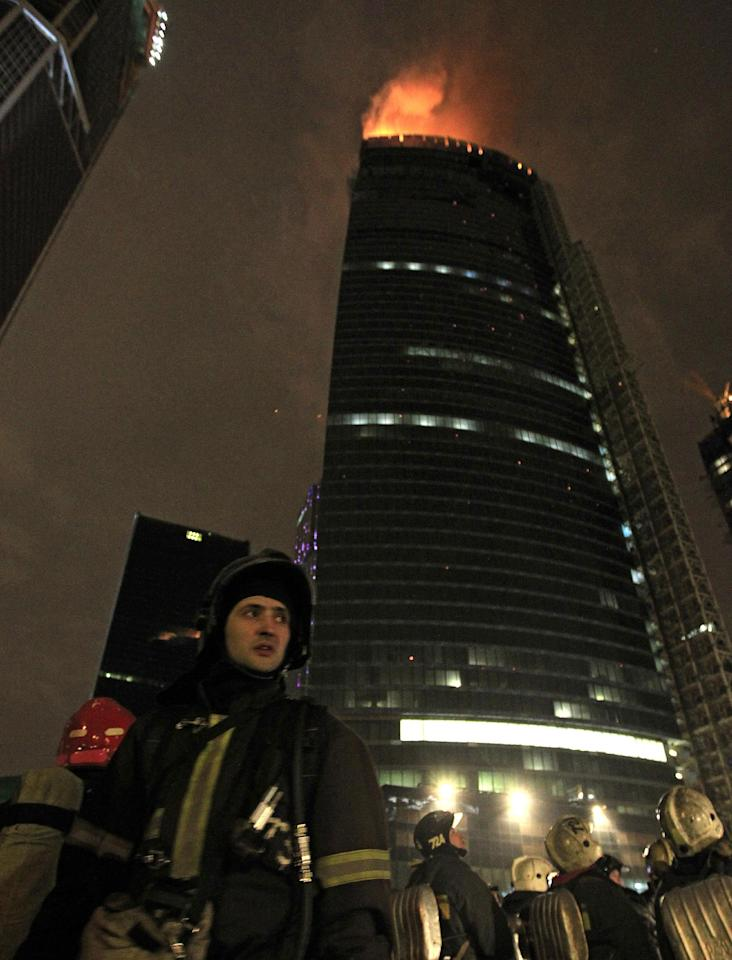 Firefighters stand near the burning under-construction skyscraper, planned to be Europe's tallest building, in Moscow, Russia, Monday, April 2, 2012. Orange flames were leaping about 250 meters (880 feet) Monday, visible in the night sky to much of the city. No injuries have been reported at the fire in the eastern tower of the Federation Tower complex, part of a massive development along the Moscow River about 2.5 kilometers (1.5 miles) west of the Kremlin. The tower, when completed, is to be 360 meters (1150 feet) tall. (AP Photo/Sergey Ponomarev)