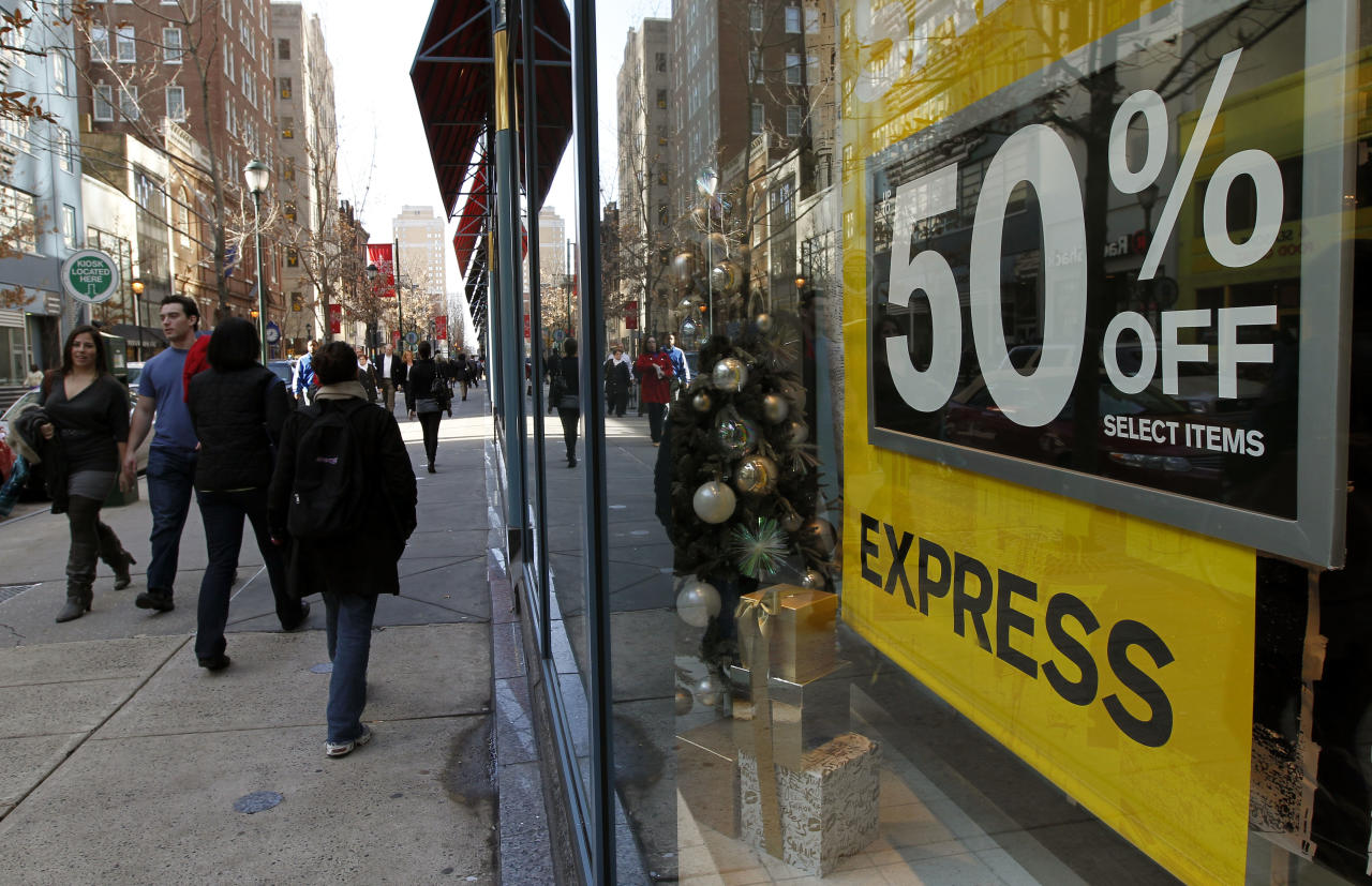 Pedestrians walk a shopping district as Express advertises a sale during the unseasonably warm weather in the few days before Christmas Thursday, Dec. 22, 2011 in Philadelphia. (AP Photo/Alex Brandon)