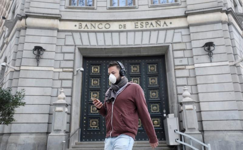 FILE PHOTO: A man wears a protective face mask as he walks past Banco de Espana (Bank of Spain), amidst concerns over coronavirus outbreak, in Barcelona