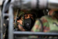 FILE PHOTO: Myanmar soldier sits inside a military vehicle in front of a Hindu temple in the downtown area, in Yangon
