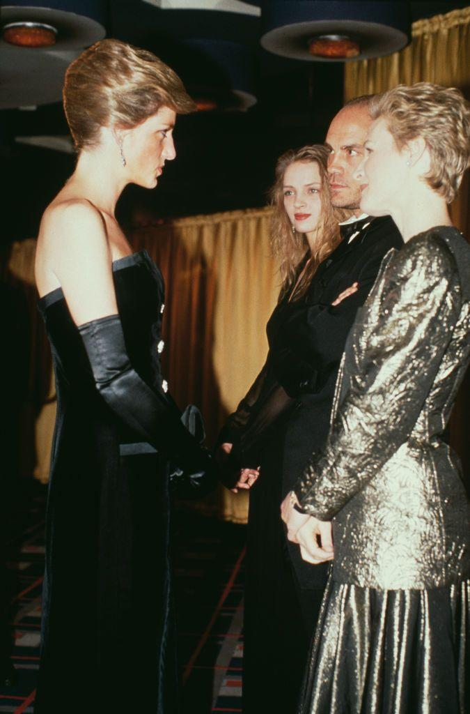 <p>At the premiere of <em>Dangerous Liaisons </em>in London, the actress wore a gold lamé dress, while Diana donned a strapless black velvet evening gown by Victor Edelstein. A young Uma Thurman can be seen waiting for her turn in the background.</p>