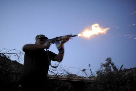 A serviceman of the Ukrainian armed forces fires a weapon in the direction of positions of units of the armed forces of the self-proclaimed Donetsk People's Republic during a battle in Avdiivka