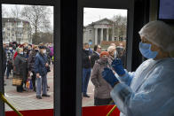 """A Russian medical worker prepares a shot of Russia's Sputnik V coronavirus vaccine as people wearing face masks to protect against coronavirus queue to get a shot of Russia's Sputnik V coronavirus vaccine in a mobile vaccination center in Simferopol, Crimea, Tuesday, April 13, 2021. Alexander Dragan, a data analyst who has been tracking vaccination in the Russian regions, says Russia is currently vaccinating 200,000-205,000 people a day. In order to immunize 30 million people by mid-June, it needs to be nearly double that: """"We need to start vaccinating 370,000 people a day, like, beginning tomorrow,"""" Dragan told the AP. (AP Photo/Alexander Polegenko)"""