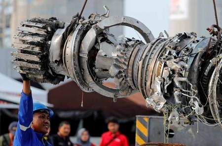 A worker assists his colleague during the lifting of a turbine engine of the Lion Air flight JT610 jet, at Tanjung Priok port in Jakarta