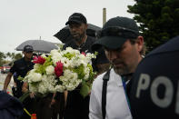 Miami Heat forward Udonis Haslem carries flowers as he arrives to pay his respects at a makeshift memorial to the people who were killed and the scores who remain missing, nearly a week after the partial collapse of the Champlain Towers South condo building, Wednesday, June 30, 2021, in Surfside, Fla. (AP Photo/Gerald Herbert)
