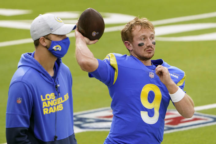 Injured Los Angeles Rams quarterback Jared Goff, left, stands next to quarterback John Wolford (9) before an NFL football game against the Arizona Cardinals in Inglewood, Calif., Sunday, Jan. 3, 2021. Jared Goff is trying to return for the Los Angeles Rams' playoff game at Seattle just 13 days after thumb surgery. If he can't go, backup John Wolford will make his second NFL start. The Rams (10-6) are confident they can win with either man behind center. (AP Photo/Jae C. Hong)