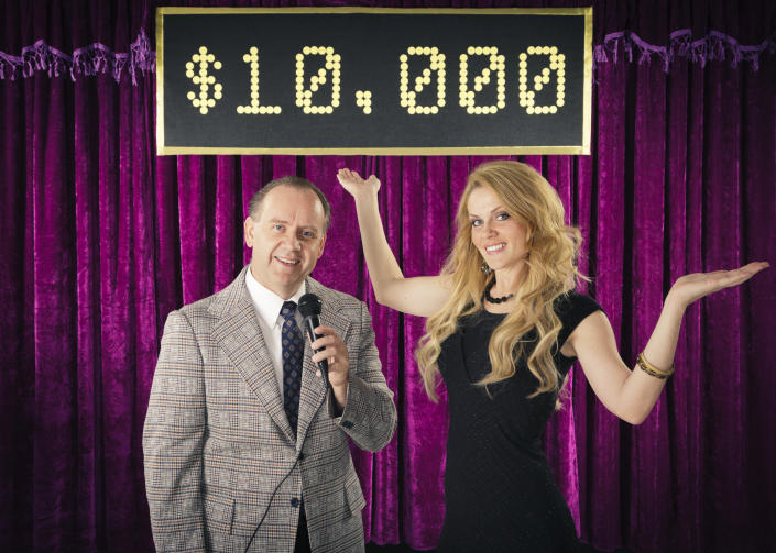 A Retro color processed game show host with his lovely assistant. Photographed in studio with a purpose built set and props.