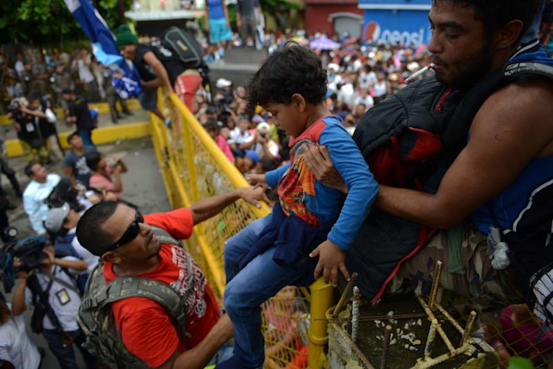 A child is passed over a border fence between Guatemala and Mexico on Friday. (Photo: ASSOCIATED PRESS)