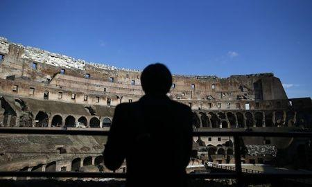 A tourist is silhouetted as he visits Rome's ancient Colosseum January 18, 2013. Italian restorers cleaning the Colosseum have discovered remains of frescoes indicating the interior of one of the world's most famous monuments may have been colourfully painted in Roman times. REUTERS/Tony Gentile (ITALY - Tags: TRAVEL SOCIETY)