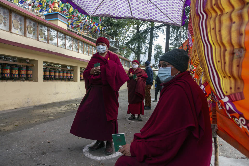 Exile Tibetan Buddhist monks and nuns maintain social distance as a precaution against the coronavirus as they stand in a queue to vote in Dharmsala, India, Sunday, Jan. 3, 2021. Exile Tibetans Sunday voted in the first round to elect a new political leader and members of the Tibetan parliament in exile. (AP Photo/Ashwini Bhatia)