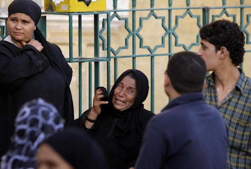 An Egyptian woman grieves during the funeral procession of four Shiites outside a mosque in Cairo, Egypt, Monday, June 24, 2013. Egypt's Islamist president condemns the killing of four Shiites by a Sunni Muslim mob that beat the men to death in their homes. But critics say he is in part to blame for implicitly supporting his hard-line allies as they stir up incitement against Shiites over Syria's civil war, and they warn that militant Islamists are acting with impunity. (AP Photo/Amr Nabil)