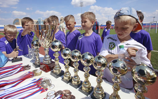 In this photo taken on Thursday, May 17, 2018, boys examine trophies during a nine-year-old children soccer tournament at the Start Stadium in Saransk, Russia. The Start Stadium in Saransk may not look like much, but its the jumping-off point for hundreds of young Russians dreams of soccer stardom. (AP Photo)
