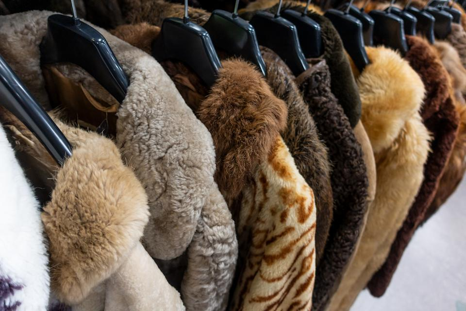 Rail of secondhand fur coats on coat hangers for sale in a thrift store or charity shop