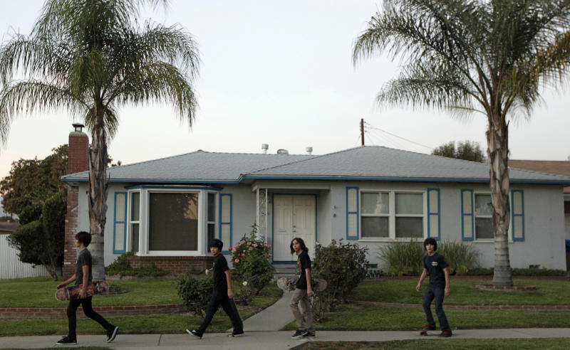 Unidentified teens walk past the home of the family of Arifeen David Gojali in Pomona, Calif., on Tuesday, Nov. 20, 2012. Three California men excited at the prospect of training in Afghanistan to become terrorists prepared, authorities say, by simulating combat with paint ball rifles, wiping their Facebook profiles of any Islamic references and concocting cover stories. Family members told The Associated Press they were shocked by Gojali's arrest, but added that the unemployed Gojali had drifted away from the family in the recent months. (AP Photo/Damian Dovarganes)
