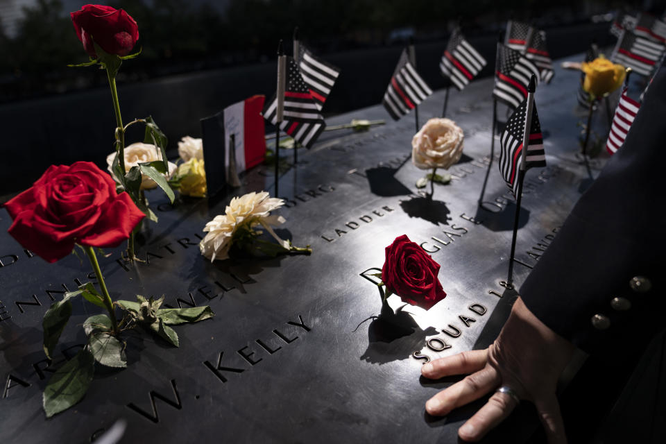 A firefighter places his hand on the name engravings on the south pool during ceremonies to commemorate the 20th anniversary of the Sept. 11 terrorist attacks, Saturday, Sept. 11, 2021, at the National September 11 Memorial & Museum in New York. (AP Photo/John Minchillo)