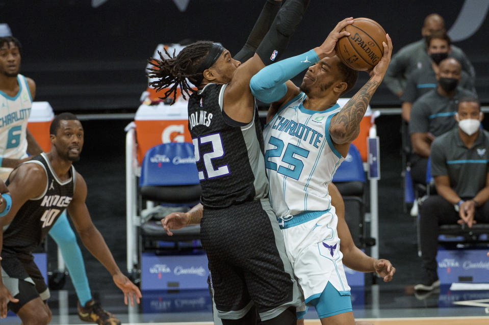 Sacramento Kings center Richaun Holmes (22) defends against Charlotte Hornets forward P.J. Washington (25) during the first quarter of an NBA basketball game in Sacramento, Calif., Sunday, Feb. 28, 2021. (AP Photo/Randall Benton)