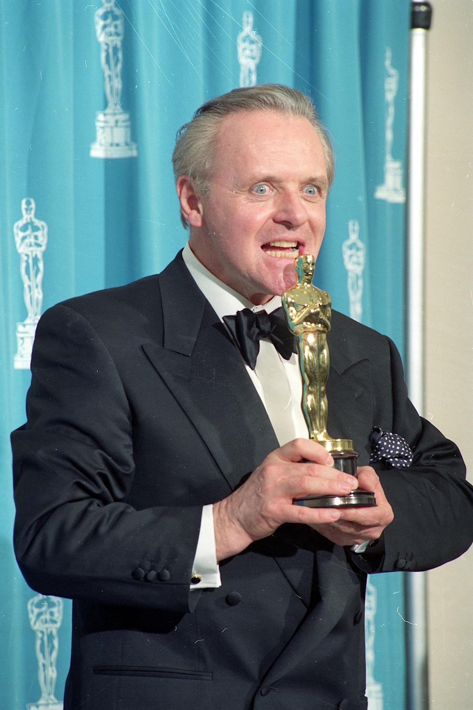 Actor Anthony Hopkins pretends to eat his Oscar Award backstage at the 64th Annual Academy Awards in Los Angeles, on Monday, March 30, 1992.  Hopkins won Best Actor honors for his portrayal of Dr. Hannibal Lecter in