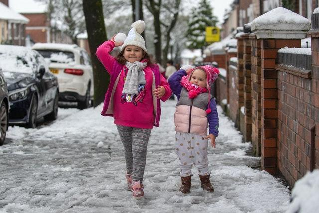 Sisters play with snowballs