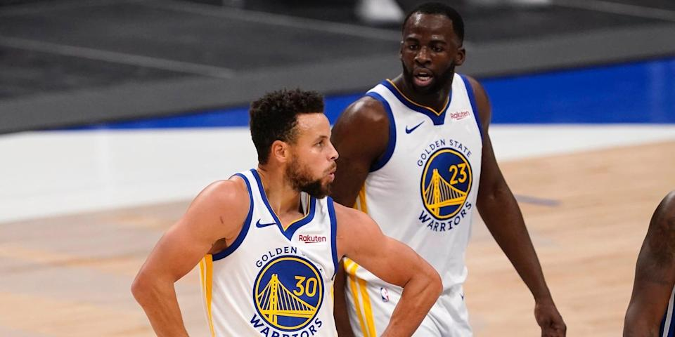 Stephen Curry celebrates while Draymond Green stands behind him.