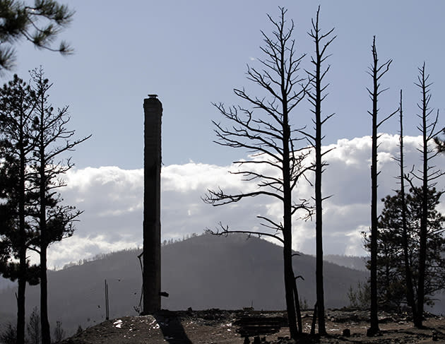 A chimney of a home destroyed by the Fourmile Canyon fire stands next to burned trees in Sunshine Canyon, west of Boulder, Colo. (Photo: AP Photo/Jae C. Hong, Pool)