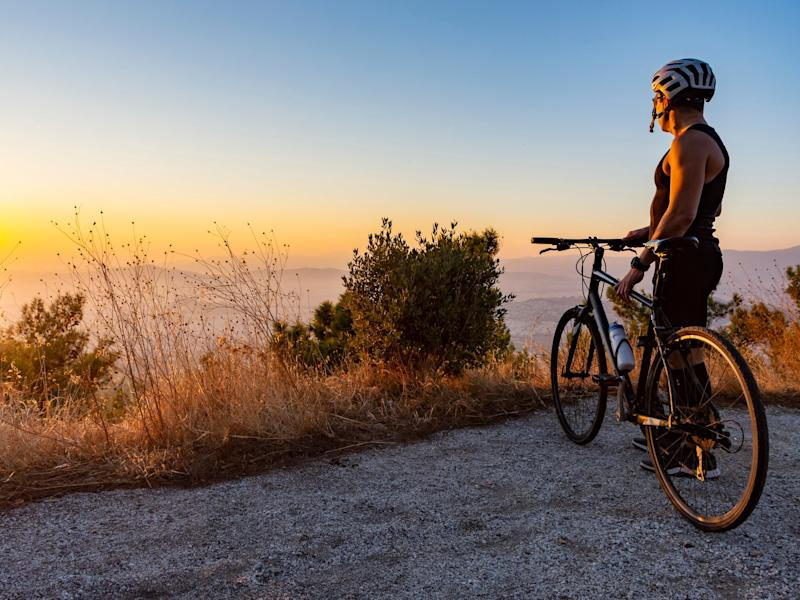 A cyclist watches the sun set in Greece: istock