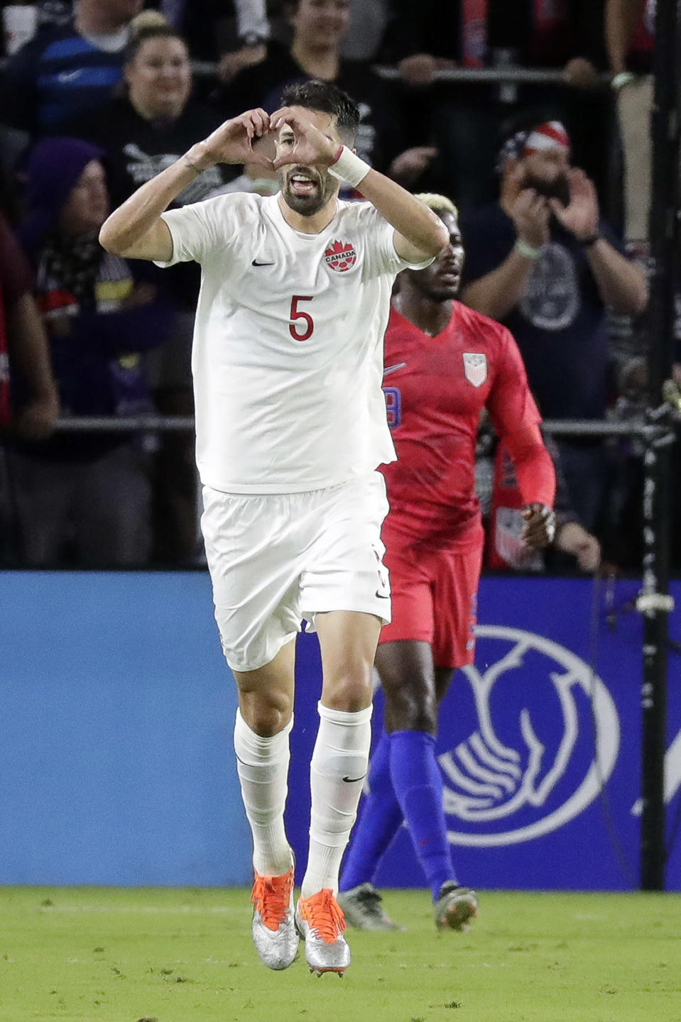 Canada defender Steven Vitoria (5) makes a heart shape with his hands after scoring a goal against the United States during the second half of a CONCACAF Nations League soccer match Friday, Nov. 15, 2019, in Orlando, Fla. (AP Photo/John Raoux)