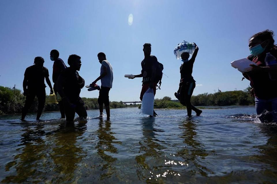 Haitian migrants use a dam to cross to and from the United States from Mexico, Friday, Sept. 17, 2021, in Del Rio, Texas.