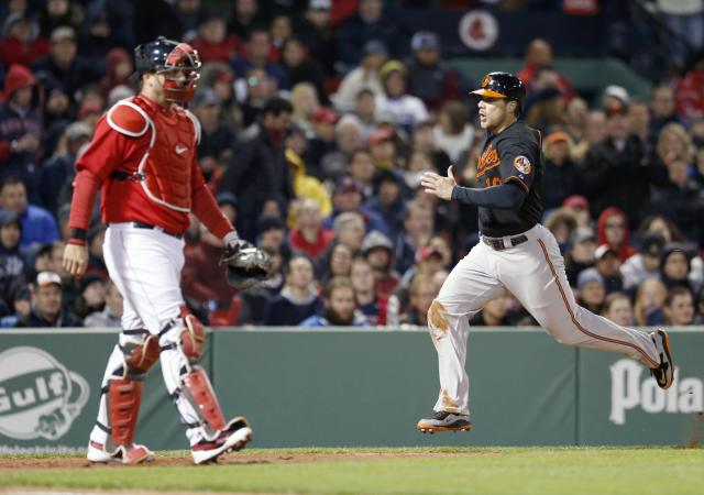 Baltimore Orioles' Chris Davis (19) scores on a two-run single by Nelson Cruz as Boston Red Sox's A.J. Pierzynski looks to the outfield in the third inning of a baseball game in Boston, Friday, April 18, 2014. (AP Photo/Michael Dwyer)