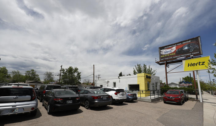 Storm clouds build over rental vehicles parked outside a closed Hertz car rental office Saturday, May 23, 2020, in south Denver. (AP Photo/David Zalubowski)
