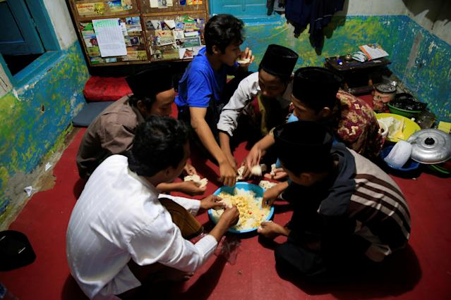 <p>Students break the fast during the holy month of Ramadan at Lirboyo Islamic boarding school in Kediri, Indonesia, May 24, 2018. (Photo: Beawiharta/Reuters) </p>