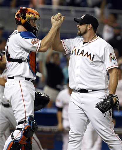 Miami Marlins relief pitcher Heath Bell, right, celebrates with catcher John Buck, left, after the Marlins defeated the Washington Nationals 3-1 in a baseball game, Tuesday, May 29, 2012, in Miami. (AP Photo/Lynne Sladky)