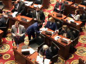Members of the Missouri House -- some wearing masks, and other not -- huddle closely in conversations before the beginning of session on Wednesday, Feb. 3, 2021, in Jefferson City, Mo. The House chamber has no mask mandate and has not modified its seating during the coronavirus pandemic. The House canceled all work for a full week in January after a COVID-19 outbreak. (AP Photo/David A. Lieb)