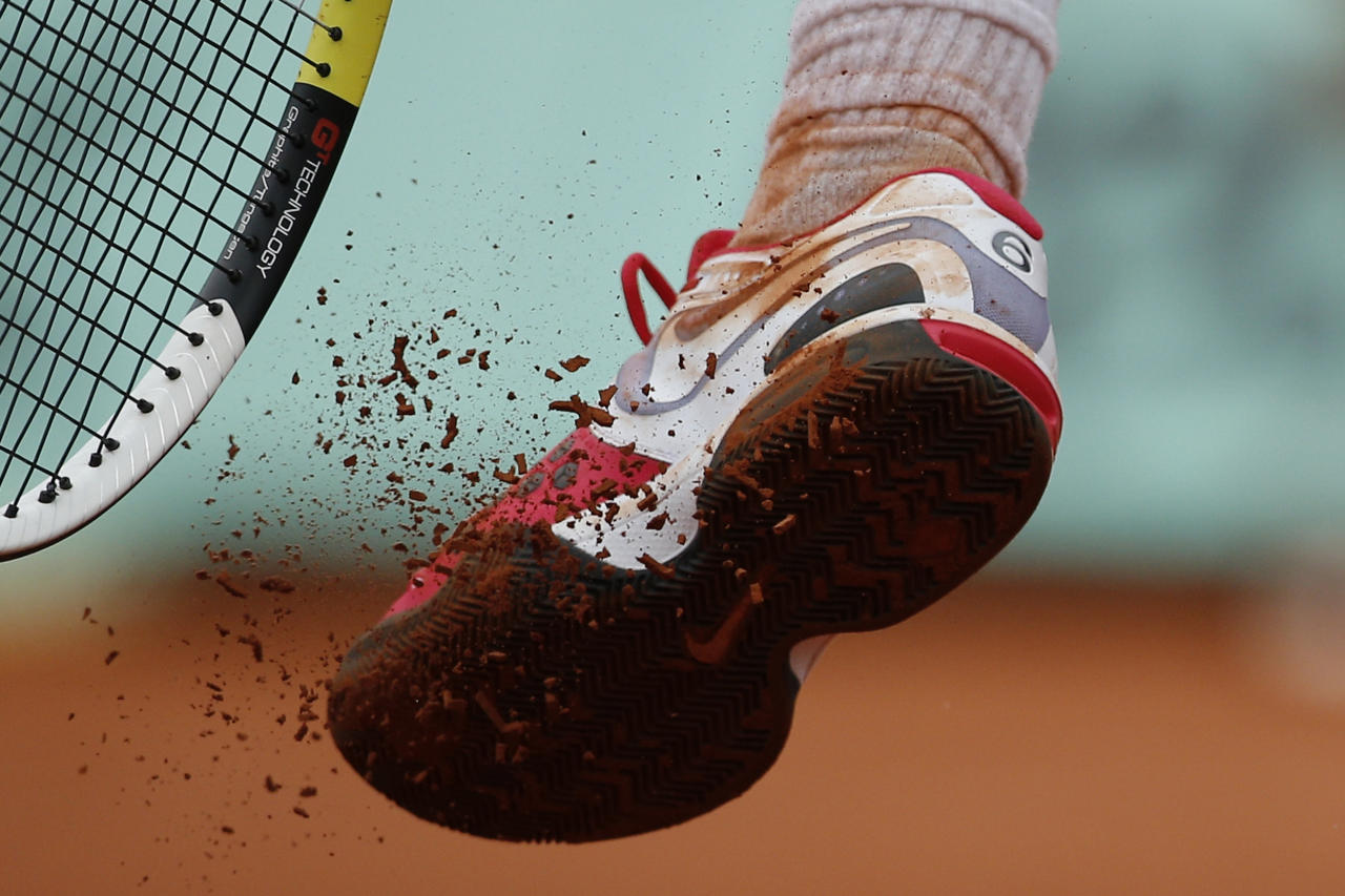 The number six marking his six previous victories at the French Open is seen on the shoe of Rafael Nadal of Spain as he kicks off the clay in his quarter final match against compatriot Nicolas Almagro at the French Open tennis tournament in Roland Garros stadium in Paris, Wednesday June 6, 2012. (AP Photo/Christophe Ena)