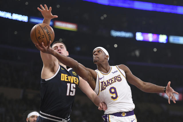 Los Angeles Lakers guard Rajon Rondo, right, attempts a layup against Denver Nuggets center Nikola Jokic during the first half of an NBA basketball game Sunday, Dec. 22, 2019, in Los Angeles. (AP Photo/Michael Owen Baker)