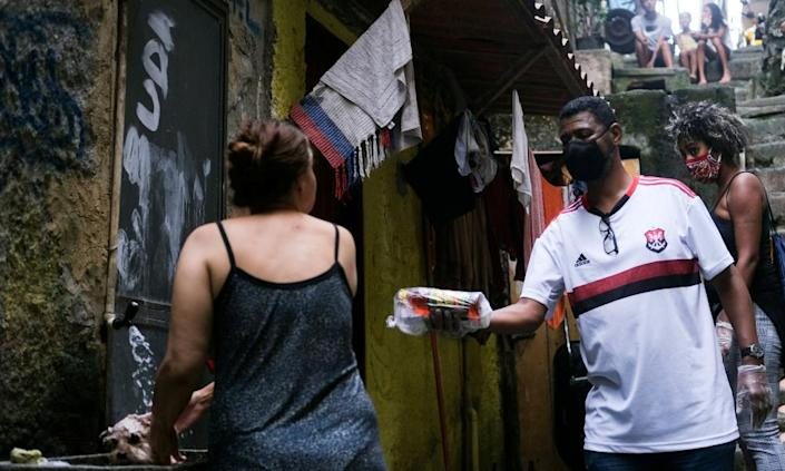 """<span class=""""element-image__caption"""">Community leader William da Rocinha, wearing a protective face mask and gloves, delivers aid donations to a resident of the Rocinha favela in Rio de Janeiro this week.</span> <span class=""""element-image__credit"""">Photograph: Ricardo Moraes/Reuters</span>"""