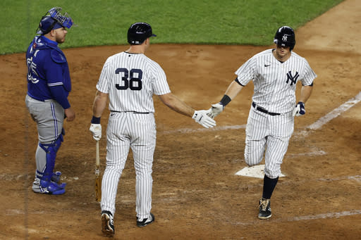 New York Yankees' DJ LeMahieu, right, is congratulated by Erik Kratz, center, after hitting a solo home run in during the eighth inning of a baseball game on Tuesday, Sept. 15, 2020, in New York. At left is Toronto Blue Jays catcher Alejandro Kirk. (AP Photo/Adam Hunger)