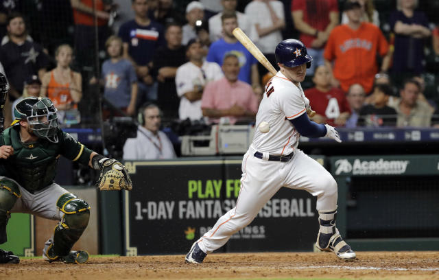 Houston Astros' Alex Bregman, right, hits a ground ball in front of Oakland Athletics catcher Jonathan Lucroy during the 11th inning of a baseball game Tuesday, July 10, 2018, in Houston. The Astros won 6-5 in 11 innings. (AP Photo/David J. Phillip)