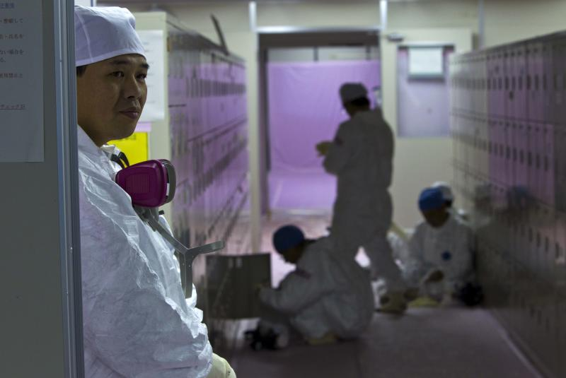 FILE - In this Nov. 12, 2011 file photo, workers in protective suits gather near their lockers inside the emergency operation center at the crippled Fukushima Dai-ichi nuclear power station in Okuma, Japan. Japanese labor officials said Sunday, July 22, 2012 that they are investigating subcontractors on suspicion they forced workers at the tsunami-hit nuclear plant to underreport their dosimeter readings so they could stay on the job longer. (AP Photo/David Guttenfelder, Pool, File)