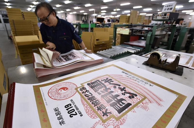 a japanese printer checks 2019 calendars which display the current era known as heisei