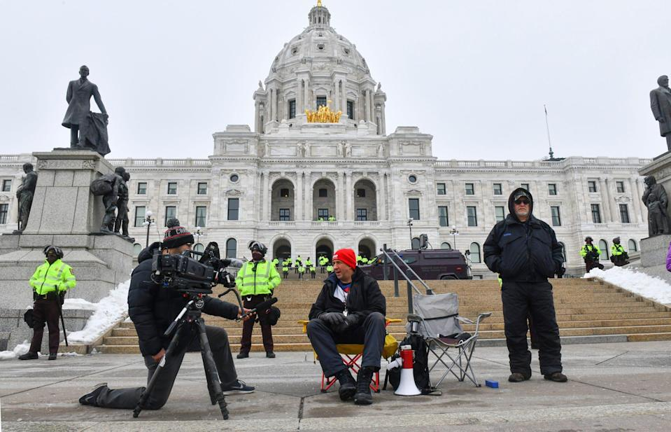 People are interviewed near a line of State Patrol officers Sunday, Jan. 17, 2021, in front of the Minnesota State Capitol in St. Paul.
