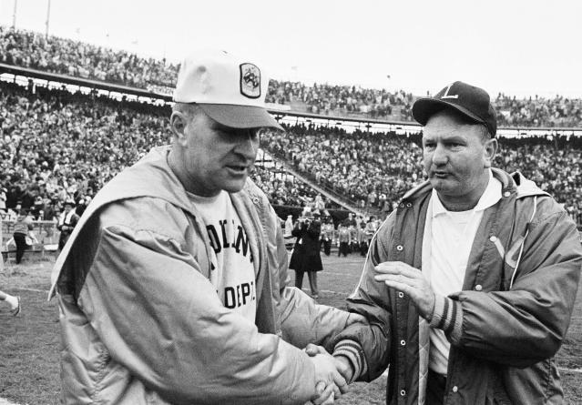 FILE - In this Jan. 1, 1968, file photo, LSU coach Charlie McClendon, right, pats the hand of Wyoming coach Lloyd Eaton in the Sugar Bowl at New Orleans. The University of Wyoming is welcoming eight former football players back on campus half a century after a racist episode gutted their team. University officials plan to unveil a plaque commemorating the Black 14 athletes at War Memorial Stadium on Friday, Sept. 13, 2019. Eaton dismissed the 14 black players after they asked Eaton if they could wear black armbands to protest racism. Black 14 members say their biggest disappointment is not hearing Eaton explain himself. Eaton died in 2007. (AP Photo/File)