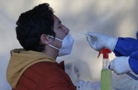 A man gets a nasal swab for a rapid COVID-19 test at a post set up in Mexico City, Saturday, Dec. 26, 2020. Mexico began applying the first dose of a COVID-19 vaccine on Dec. 24 produced by Pfizer and its German partner BioNTech as people are still getting tested for COVID-19. (AP Photo/Ginnette Riquelme)