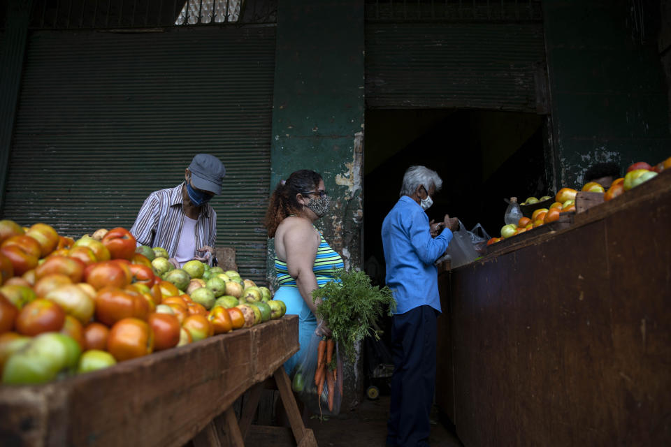 Yuliet Colon, center, waits to check-out at an agricultural market near her home, in Havana, Cuba, Friday, April 2, 2021. Colon is among several Cubans who, with more ingenuity than resources, help their compatriots cope with shortages exacerbated by the new coronavirus pandemic with Facebook posts of culinary creations designed around what they're actually likely to find at the market or with government rations. (AP Photo/Ramon Espinosa)
