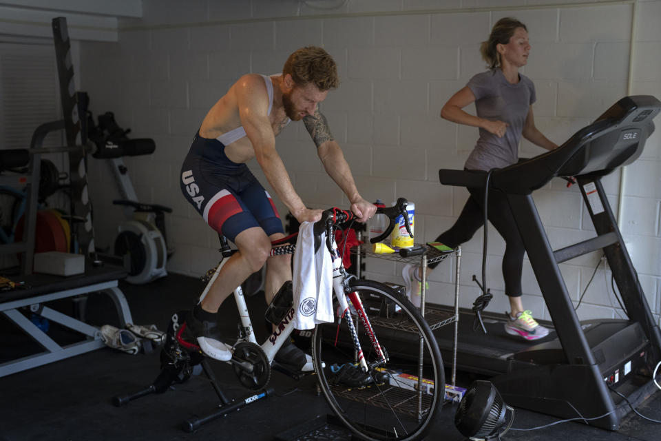 Brad Snyder, who lost his sight in Afghanistan in 2011, works out with his wife, Sara, in their garage in Princeton, N.J., on Thursday, Aug. 5, 2021. They met a few years ago through a friend. She is, he says, the most beautiful woman in the world. He has never seen her. (AP Photo/Emilio Morenatti)